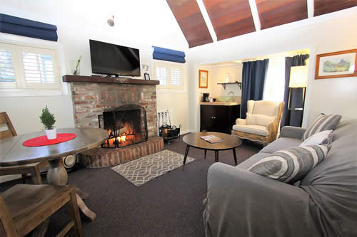 carmel boutique inn guestroom - fireplace, couch, TV chairs and table