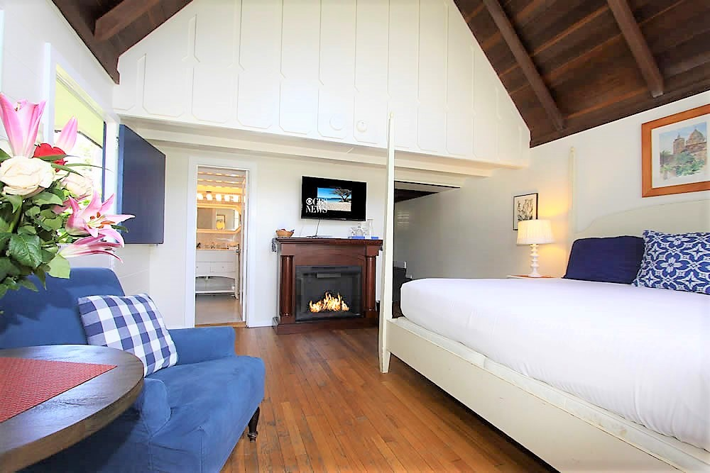 four poster bed, chairs, tall windows, fireplace