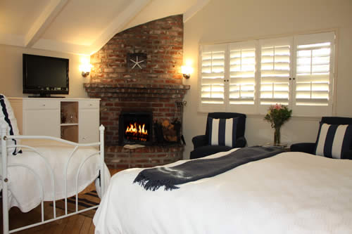 carmel boutique inn guestroom - bed, chairs and table, fireplace