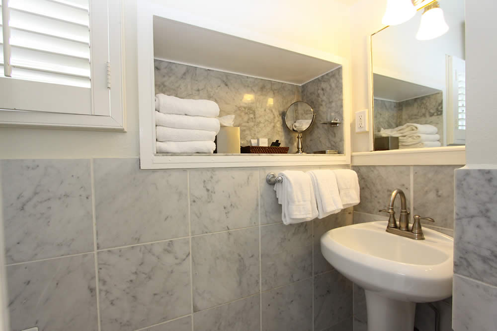 bathroom with mable walls, sink and white towels