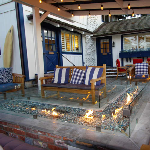 carmel boutique inn courtyard with glass fireplace, sitting chairs and surfboard