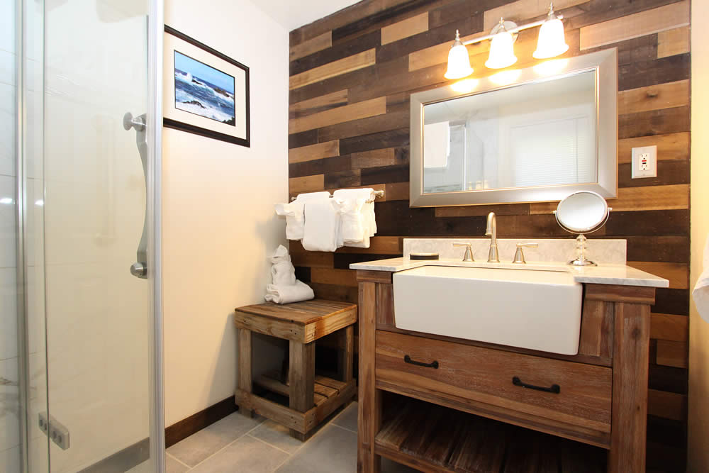 bathroom with sink and shower plus wood paneling
