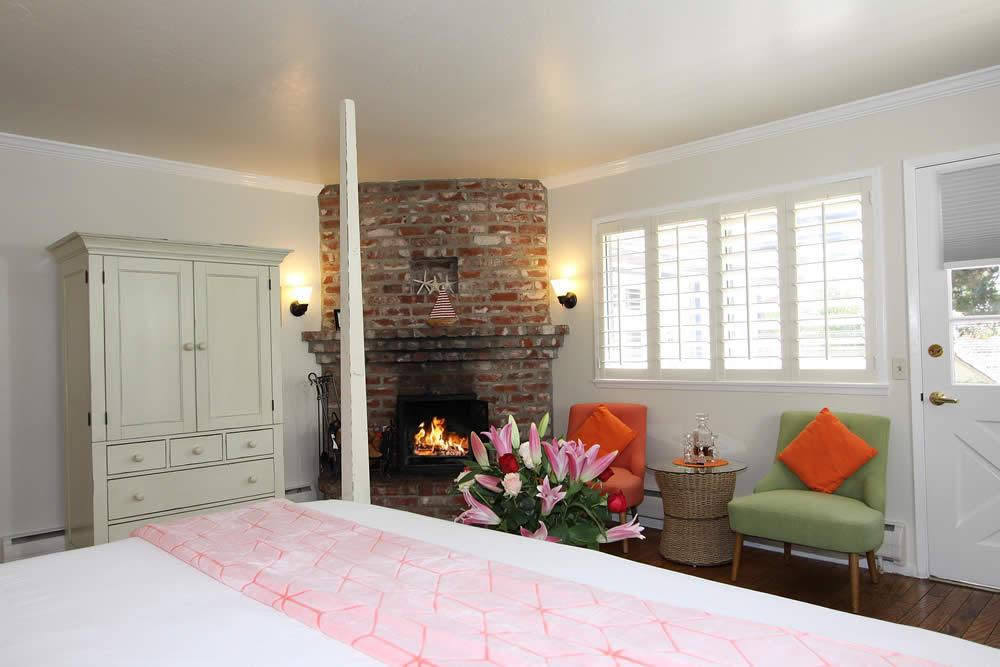 bed, fireplace, two green chairs and cabinet