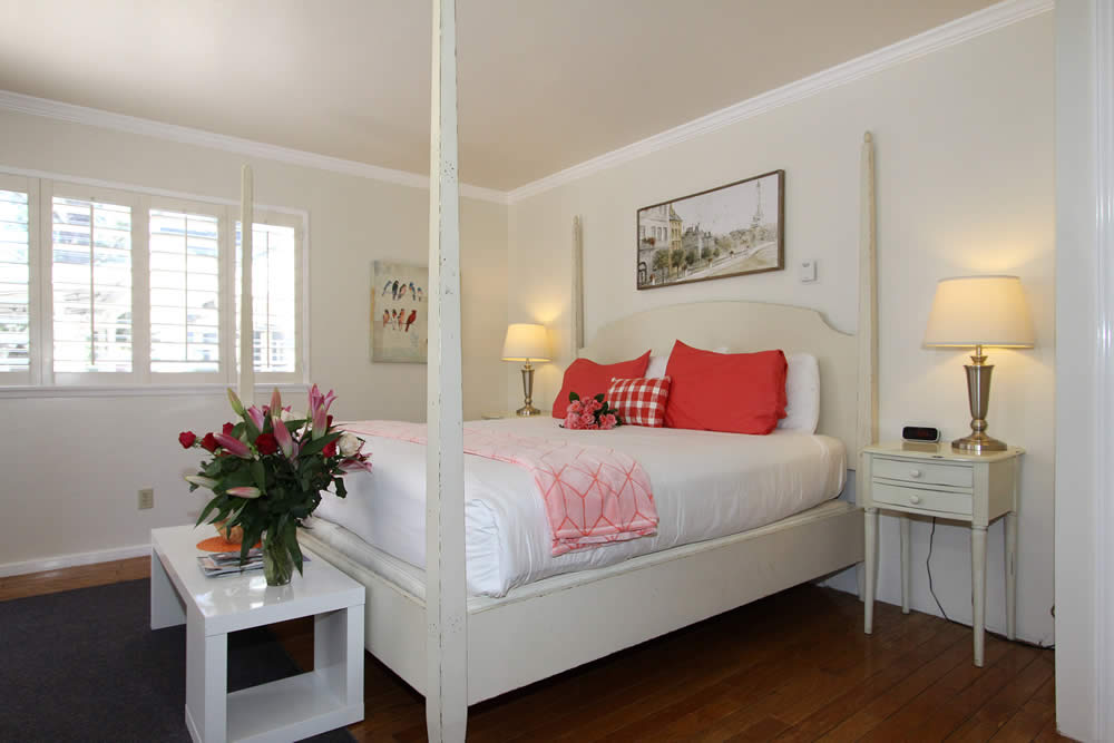 four poster bed with orange pillows and flowers on foot table