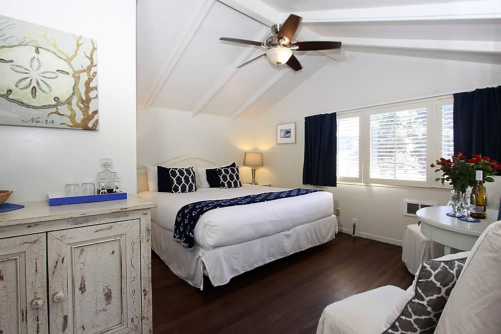bed, chairs, cabinet with ceiling fan