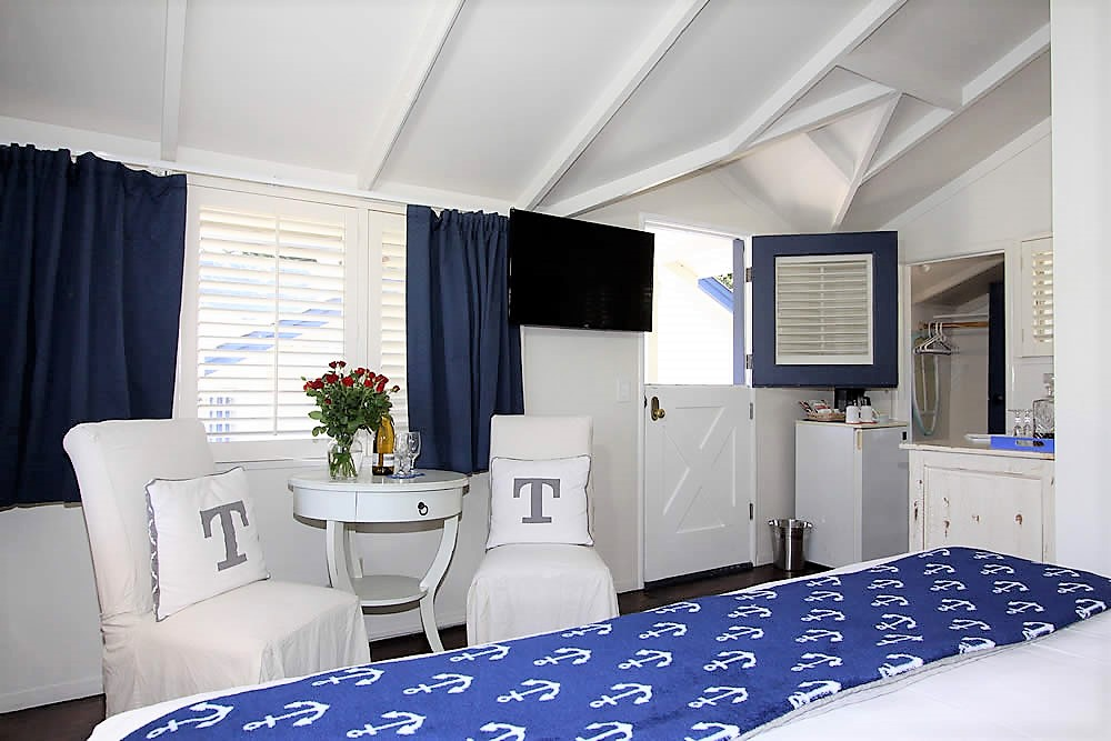 bed, tv, chairs with pillows and dutch door