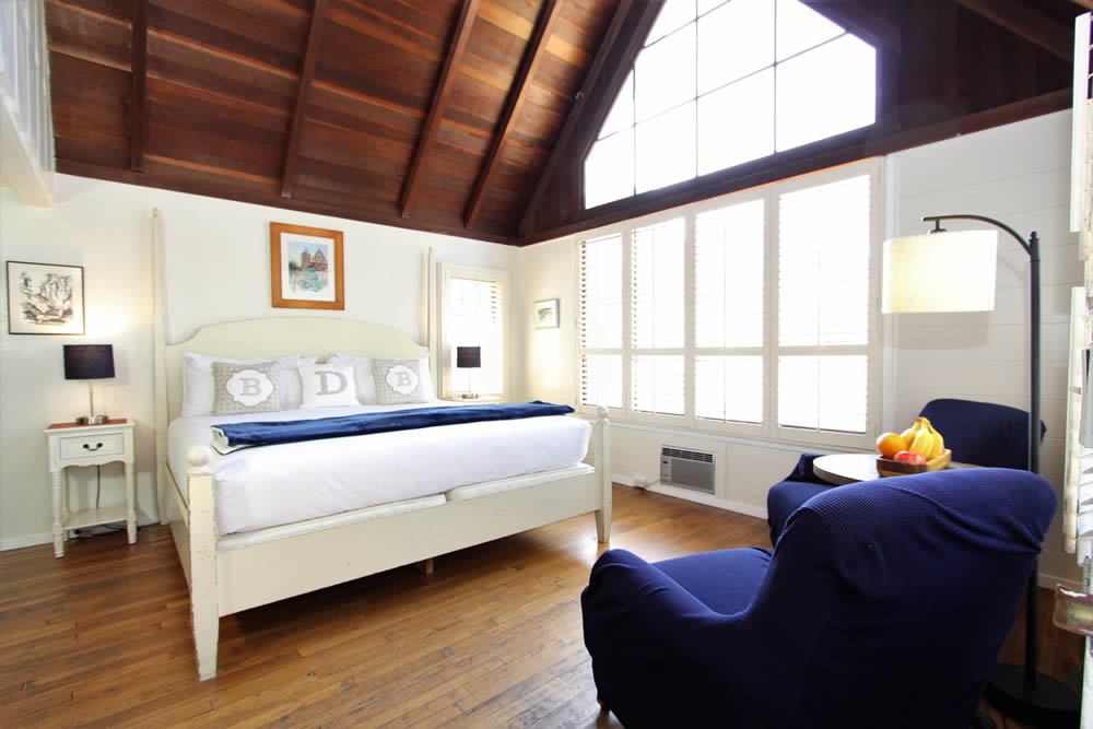 blue bird cottage with bed chairs and windows