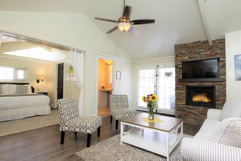 concours suite with king bed, couch, table and chairs with fireplace